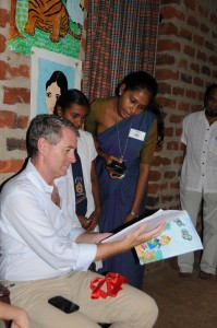 Room to Read founder John Wood admires a book that Maheshika has written and illustrated herself.